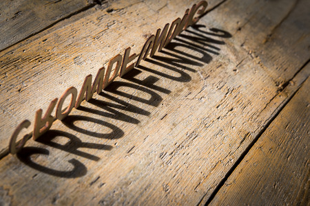 wooden letters on old aged wooden table build the shadow word crowdfunding, vintage style Foto de archivo