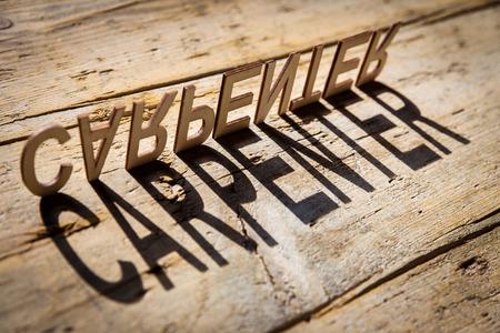 carpintero: letras de madera en la vieja mesa de madera envejecida construyen la palabra sombra carpintero, estilo vintage