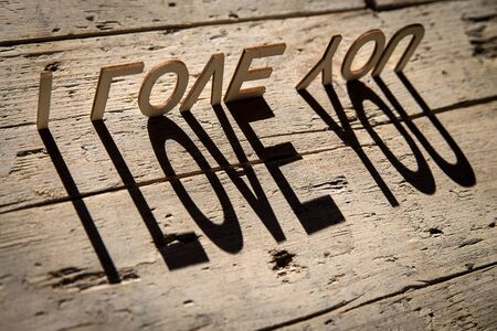 i love you sign: wooden letters on old aged wooden table build the shadow word i love you, vintage style