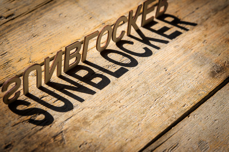dermal: wooden letters on old aged wooden table build the shadow word sunblocker, vintage style