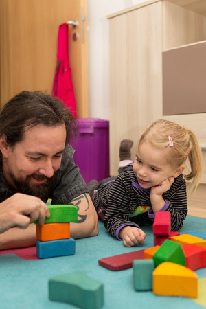 exhibiting: Father exhibiting colorful bricks to his cute daughter