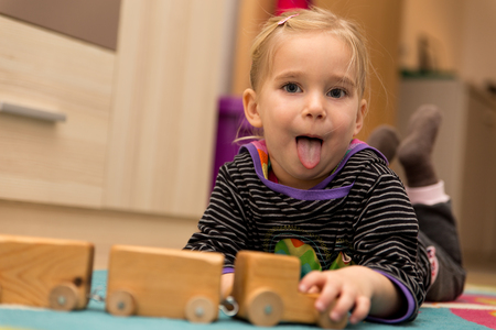 cheeky: Cheeky blond girl is playing with a wooden toy