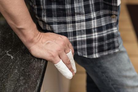 splint: hombre con los dedos lesionados se está inclinando en una mesa Foto de archivo
