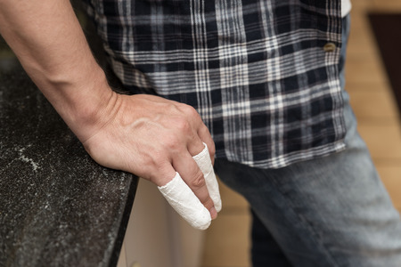 splint: man with injured fingers is leaning at a table
