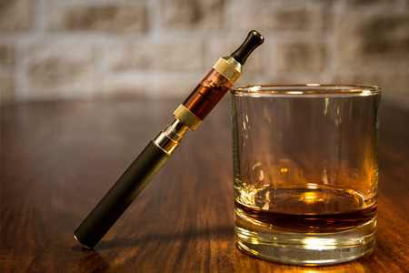 vaporizer: vintage still life with electronic cigarette and a glass of rum Stock Photo