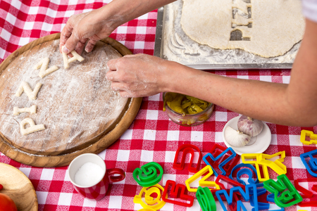 griddle: woman cuts out letters, dough on a griddle, red white tablecloth