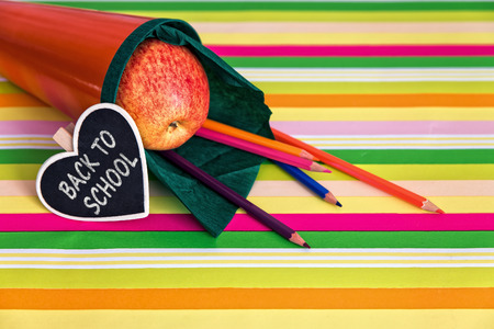 orange school bag with text back to school, lot of colorful crayons photo