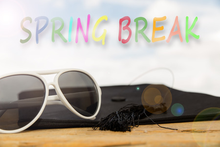 mortarboard: sunny background with mortarboard, sun glasses, and the word spring break Stock Photo