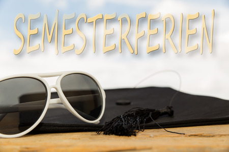 spring break: sunny background with mortarboard, sun glasses and the german word for spring break Stock Photo
