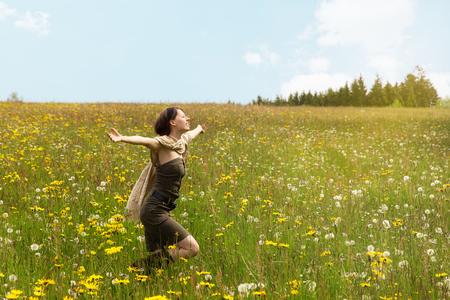 yellow wildflowers: Beautiful woman running across a wildflower meadow