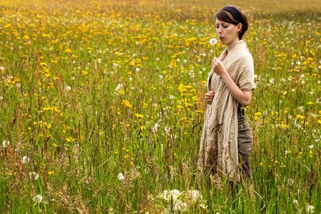 fiori di campo: bella donna con un dente di leone in un fiore di campo prato colorato Archivio Fotografico
