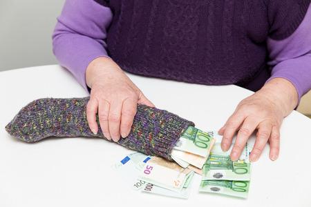 female senior adult: female senior adult with her savings in a sock
