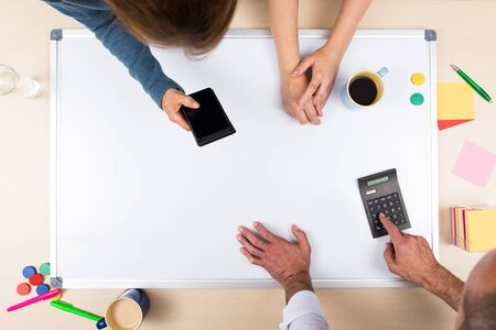 three persons: whiteboard with copy space, three persons, top view, concept business Stock Photo