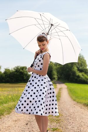 petticoat: vintage fifties look with petticoat dress, hairband und sunshade in the nature Stock Photo