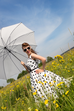 petticoat: Rockabilly or Pin up Girl with a white Petticoat dress and a umbrella in a wildflower meadow Stock Photo