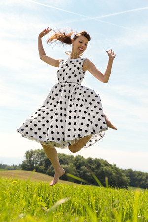 petticoat: Pin up Girl with white petticoat dress is jumping in the meadow