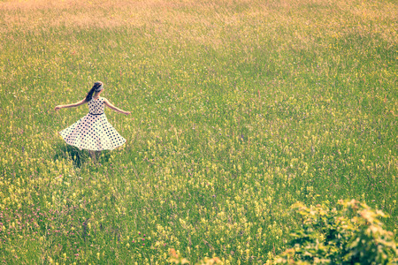 Woman with a cute vintage outfit from the fifties is dancing on the wildflower meadow, golden hour