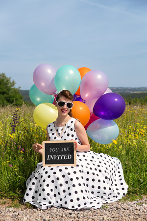invited: young women in a 50´s dress and colorful balloons an the road, board with text you are invited, concept invitation