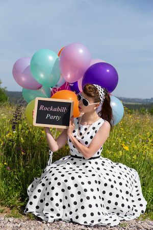 petticoat: beautiful woman with a petticoat dress holding a slate with text Rockabilly Party, concept invitation und party Stock Photo