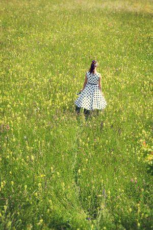 fiori di campo: Rockabilly con un abito sottoveste bianco a piedi attraverso un prato di fiori selvatici, backview Archivio Fotografico