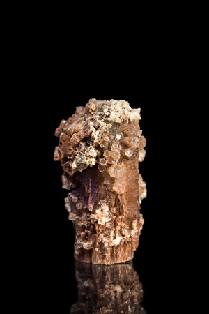 brown background: Aragonite gemstone with reflection, mineral stone for alternative healing, black background