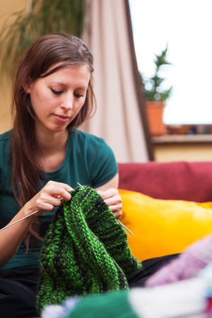 knitting: pretty young knitting woman on a couch