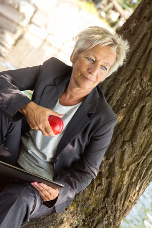 professional woman: business woman sitting on a tree and eating an apple, concept healthy nutrition