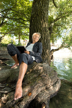reputable: beautiful older businesswoman with tablet sitting on the water and making a break
