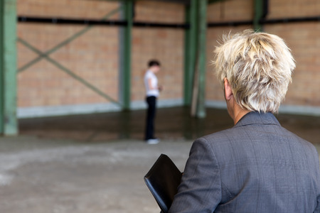 workmate: older Business woman is inspecting a warehouse, younger workmate in the background