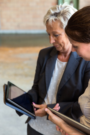 reputable: two business women with tablets are standing in a warehouse