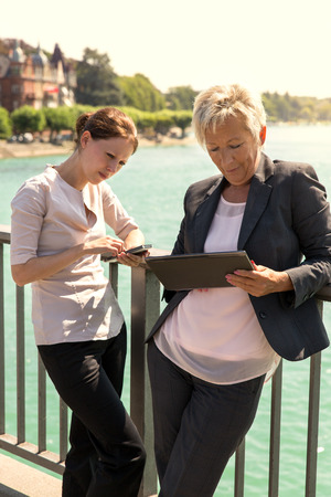 business trends: two business women with tablet and smartphone working outside the office, concept: business trends Stock Photo