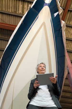 quota: businesswoman with a Tablet in front of a boat in a shipyard Stock Photo