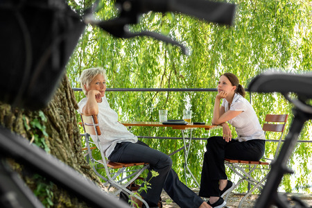 beer garden: younger and older business woman sitting in a beer garden and making a break Stock Photo
