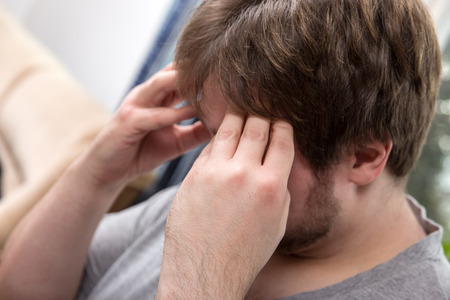 a young man at home with headache