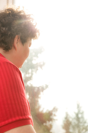 mentally: a mentally disabled woman looking out of the window Stock Photo