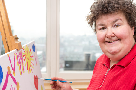 a painting Therapy with a mentally disabled woman Standard-Bild