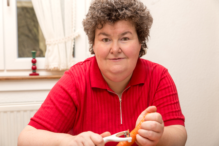 biologically: a mentally disabled woman is peeling carrots