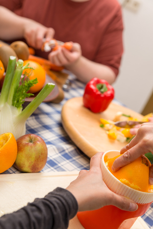 eating fruit: two persons are cooking together with a lot of fresh fruits and vegetables