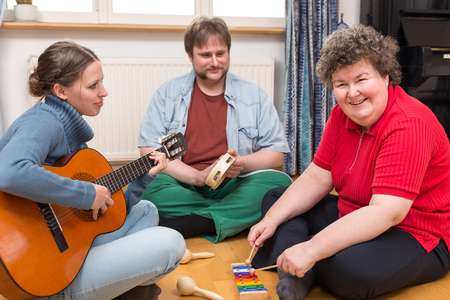 therapy group: two caretaker and a mentally disabled woman makes a music therapy