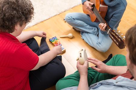 terapia de grupo: tres personas que tocan instrumentos diversos en el hogar