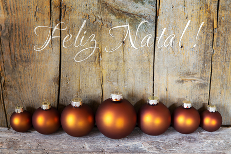 natal: seven copper colored christmas balls in front of a wooden wall, portuguese words for merry christmas, feliz natal Stock Photo