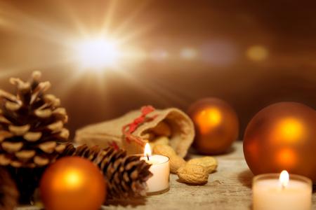 candela: Decorazione festa di Natale in arancione e bianco, candele fulmini, pigne, palline di natale e fondo in legno Archivio Fotografico