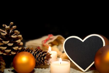 velas de navidad: Decoración de Navidad festiva en velas de color naranja y blanco, rayos, piñas, bolas de Navidad y fondo de madera