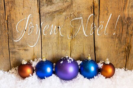 joyeux: postcard with xmas balls in front of wooden wall, french words for merry christmas, joyeux noel