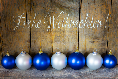 weihnachten: christmas postcard with balls in blue and white, german words for merry christmas, frohe weihnachten