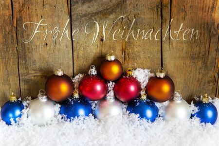 weihnachten: wooden background with colorful christmas balls with snow, german words for merry christmas, frohe weihnachten