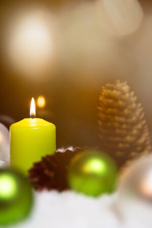 fir cones: Festive christmas decoration in green, lightning candles, fir cones and snow on the ground