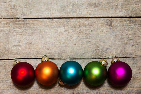 new ball: five christmas balls on wooden background, in the colours red, orange, blue, green and pink