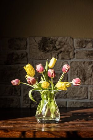 tulips in vase: a vase with a lots of tulips on the table Stock Photo
