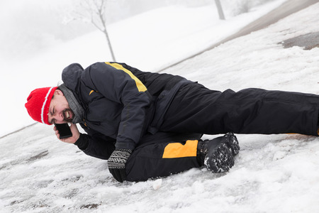Casualty man on a icy street is calling the ambulance Stock Photo